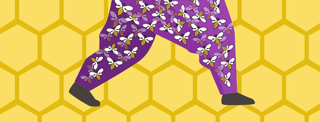 Legs filled with buzzing bees walking in front of honeycomb.